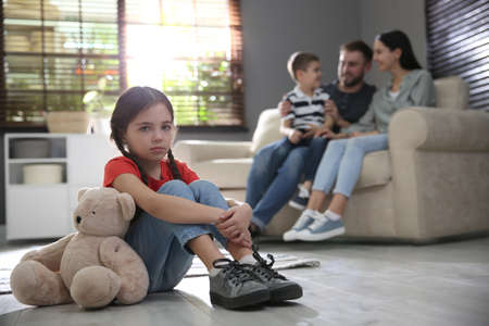 Unhappy little girl feeling jealous while parents spending time with her brother at home Stock Photo