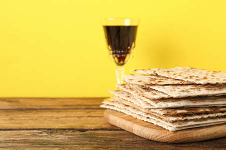 Passover matzos and glass of wine on wooden table, space for text. Pesach celebration