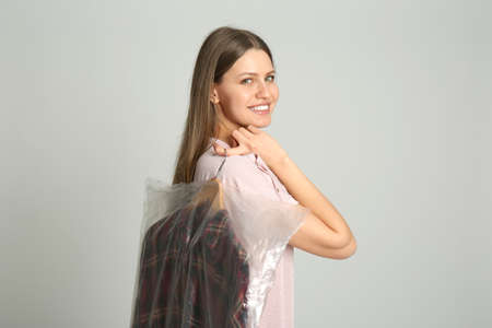 Young woman holding hanger with shirt in plastic bag on light grey background. Dry-cleaning service