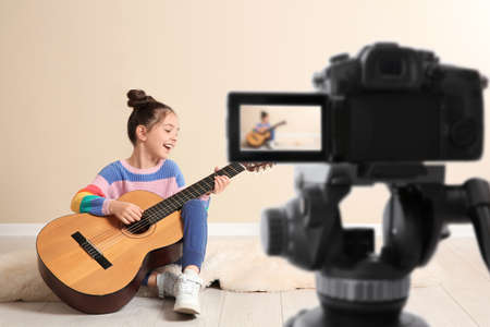 Little music teacher recording guitar lesson indoors Фото со стока