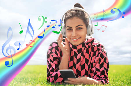 Young woman with headphones listening music outdoors