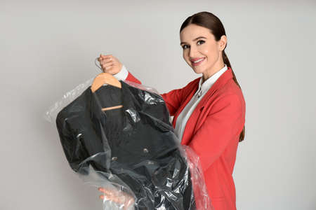 Young woman holding hanger with dress on light grey background. Dry-cleaning service
