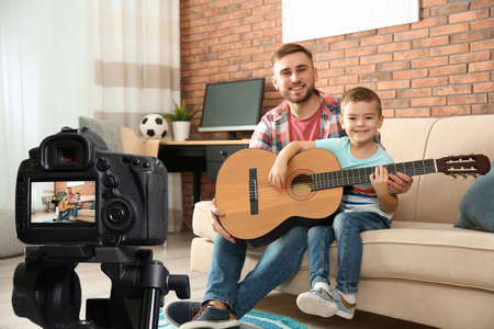Father and son recording guitar lesson indoors. Teaching music Stockfoto