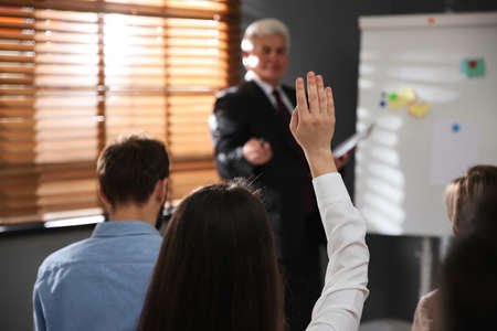 Woman raising hand to ask questions at seminar in office