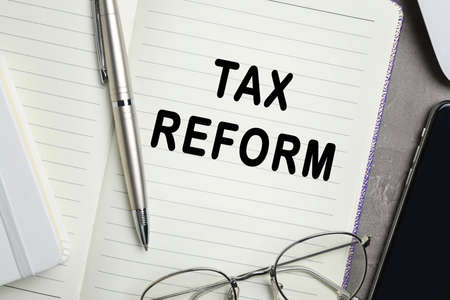 Notebook with words TAX REFORM, pen and glasses on table, closeup