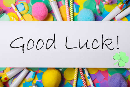 Phrase GOOD LUCK written on white note and party decor, top view Stock Photo
