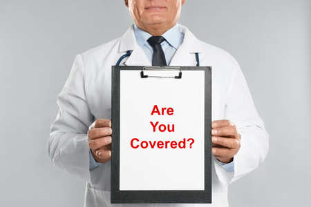 Doctor holding clipboard with text ARE YOU COVERED? on light background, closeup. Insurance concept