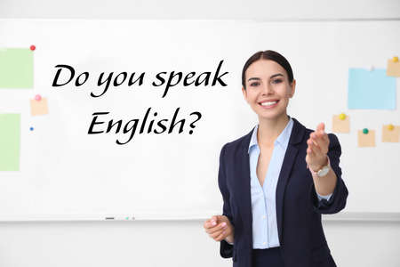 Young English teacher near whiteboard in classroom Banque d'images