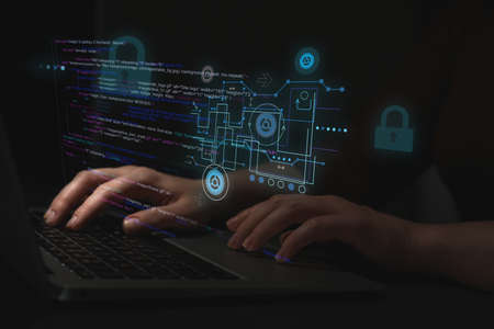 Hacker working with laptop at table, closeup. Cyber attack