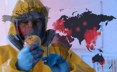 Scientist in chemical protective suit with apple and syringe at laboratory. Vaccine research