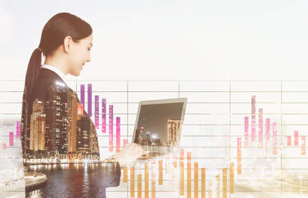 Double exposure of businesswoman with laptop and cityscape. Forex trading Stok Fotoğraf