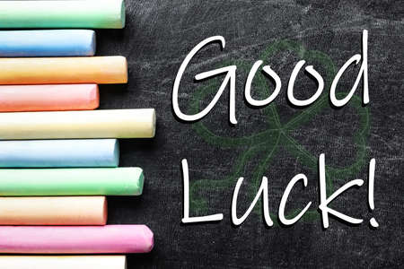 Pieces of color chalk and phrase GOOD LUCK on blackboard, flat lay