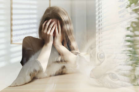 Woman suffering from ailurophobia indoors. Irrational fear of cats
