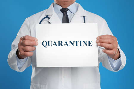 Doctor holding sign with text QUARANTINE on blue background, closeup. Stay at home during coronavirus outbreak Фото со стока