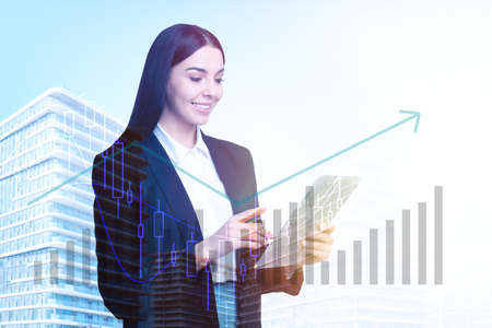 Double exposure of businesswoman with tablet and cityscape. Forex trading Foto de archivo
