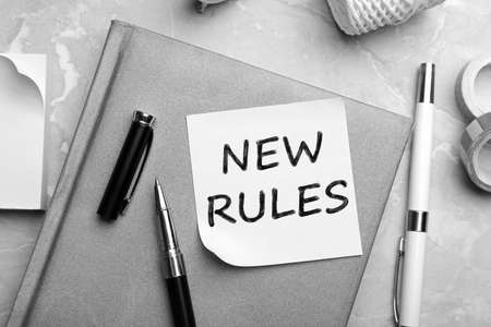 Reminder note with text NEW RULES and stationery on table, flat lay