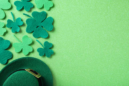 Flat lay composition with clover leaves on light green background, space for text. St. Patrick's Day celebration