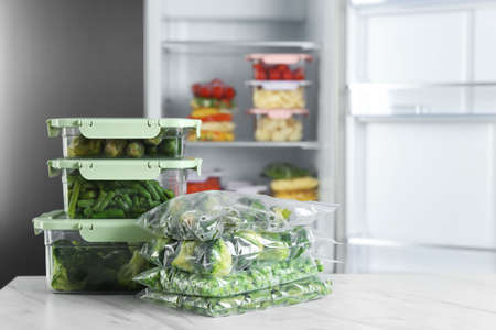 Different frozen vegetables on white marble table near open refrigerator