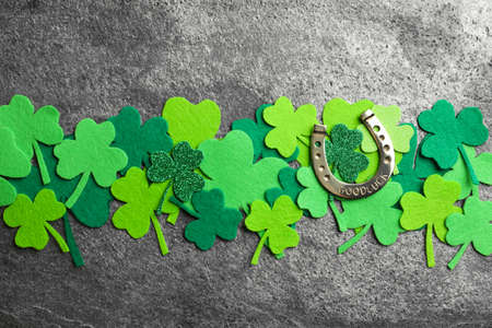 Flat lay composition with clover leaves and horseshoe on grey stone background. St. Patrick's day