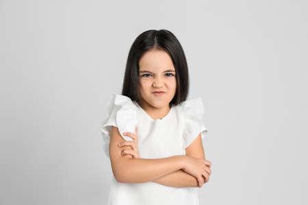 Portrait of cute little girl on light grey background