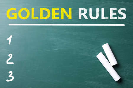 Pieces of white chalk on green chalkboard with phrase GOLDEN RULES, flat lay