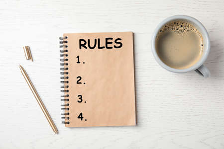 Notebook with list of rules and cup of coffee on wooden background, flat lay