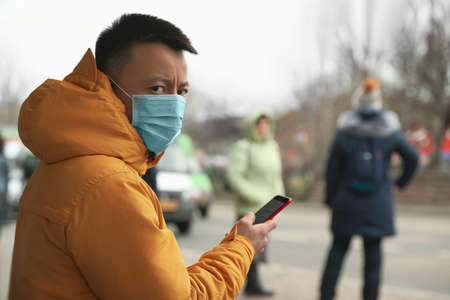 Asian man with smartphone wearing medical mask on city street, space for text. Virus outbreak Banco de Imagens