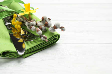 Closeup view of cutlery set with floral decor on white wooden table, space for text. Easter celebration