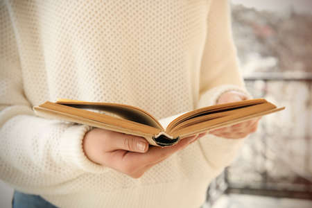 Woman reading book outdoors on sunny day, closeup