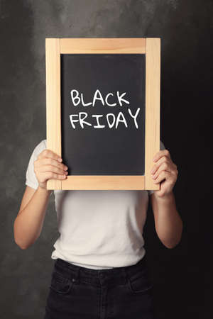 Woman holding blackboard with text BLACK FRIDAY on dark background