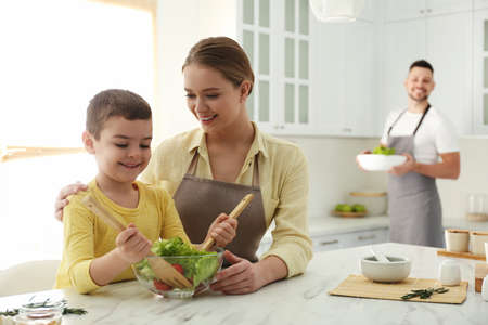 Happy family cooking salad together in kitchen Фото со стока
