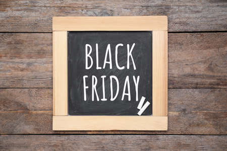 Blackboard with text BLACK FRIDAY and pieces of chalk on wooden background, top view 版權商用圖片
