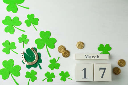 Flat lay composition with clover leaves and block calendar on white wooden background, space for text. St. Patrick's day