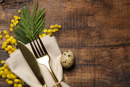 Top view of cutlery set with quail egg and floral decor on wooden table, space for text. Easter celebration Stok Fotoğraf