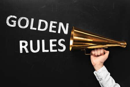 Man holding retro megaphone near chalkboard with phrase GOLDEN RULES, closeup