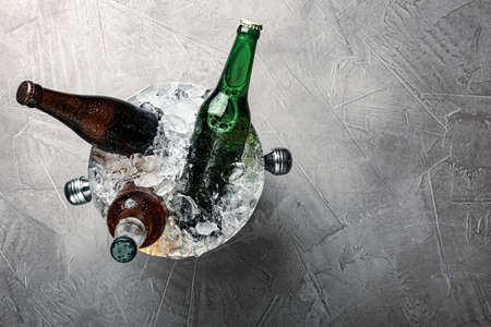 Beer in metal bucket with ice on grey table, top view. Space for text Фото со стока