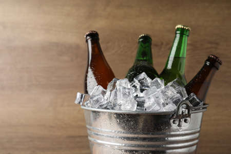 Metal bucket with beer and ice cubes on wooden background. Space for text Фото со стока