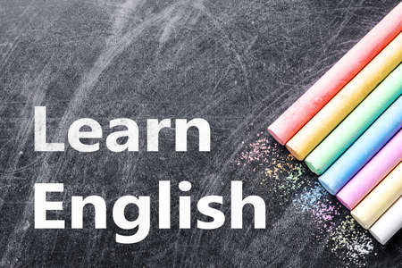 Pieces of color chalk on blackboard, flat lay. Learn English