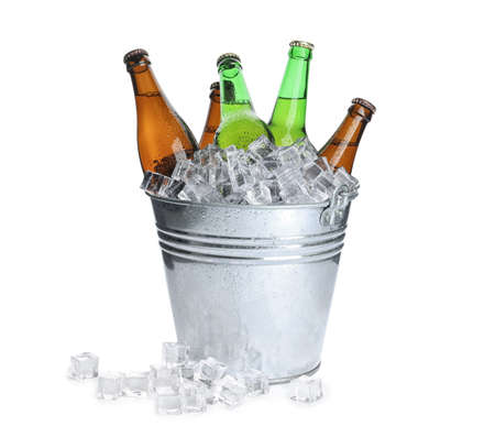 Metal bucket with bottles of beer and ice cubes isolated on white Фото со стока