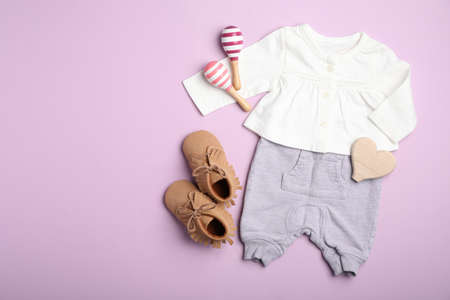 Flat lay composition with child's clothes on pink background, space for text Stockfoto