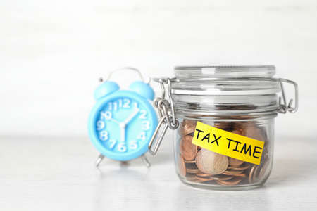 Time to pay taxes. Coins in glass jar with label on table