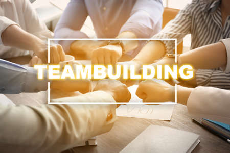 People putting hands together at table. Teambuilding concept