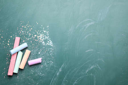 Pieces of color chalk on greenboard, flat lay. Space for text