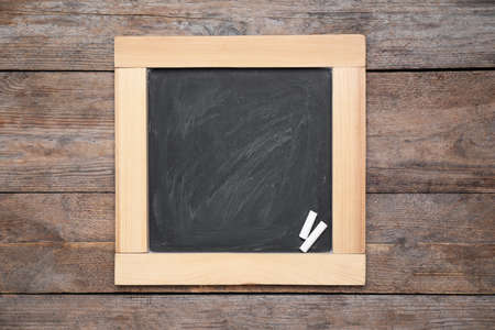 Blackboard with pieces of chalk on wooden background, top view. Space for text