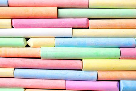Many pieces of color chalk as background, top view
