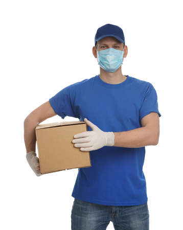 Courier in protective mask and gloves holding cardboard box on white background. Delivery service during coronavirus quarantine