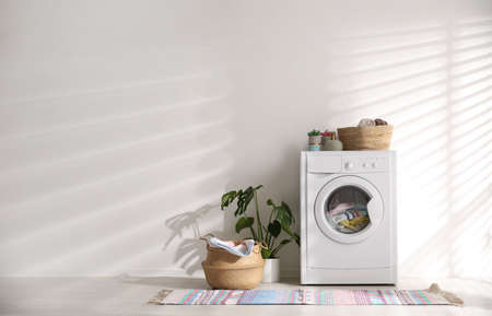 Modern washing machine and wicker basket with laundry near white wall, space for text. Interior design