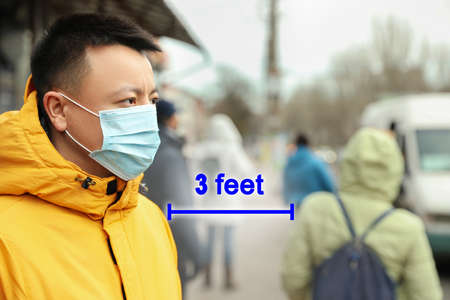 Asian man wearing mask outdoors. Social distancing during coronavirus outbreak