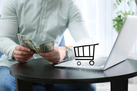 Online shopping. Cart illustration near laptop and man counting money indoors Фото со стока
