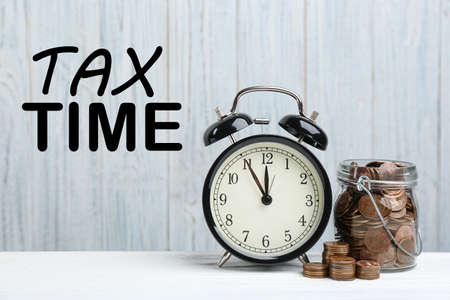 Time to pay taxes. Alarm clock, glass jar and coins on white table